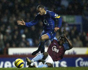 Aston Villas Djemba Djemba möter Thierry Henry i en närkamp.
